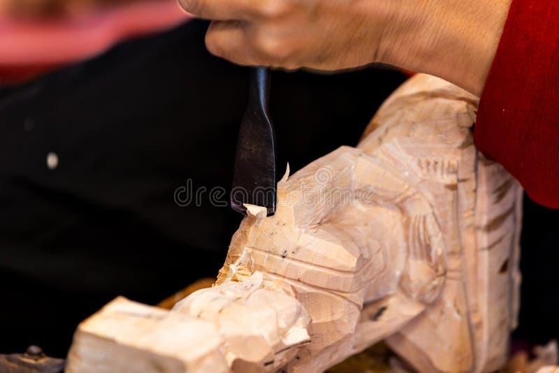 木匠的手的特写镜头与凿子和锤子一起使用在木菩萨雕塑 免版税库存图片
