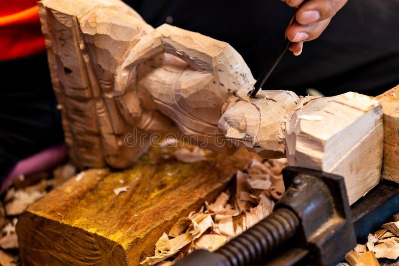 木匠的手的特写镜头与凿子和锤子一起使用在木菩萨雕塑 库存图片