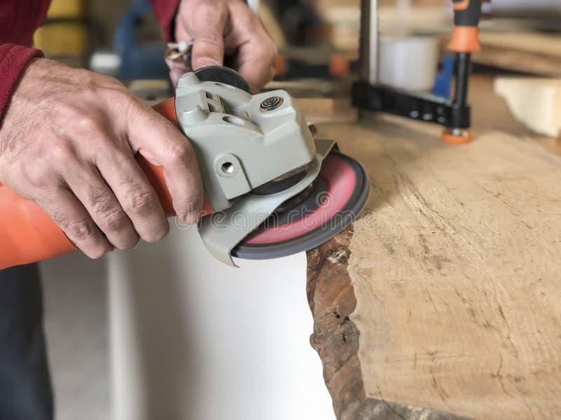 木匠的特写镜头手与金刚砂轮一起使用 免版税库存照片