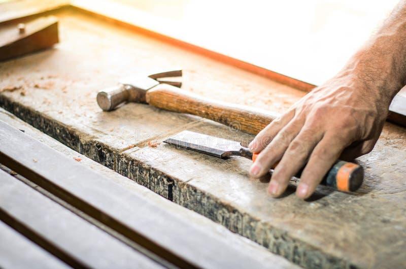 木匠的特写镜头递与凿子和锤子一起使用在木工作凳 免版税图库摄影