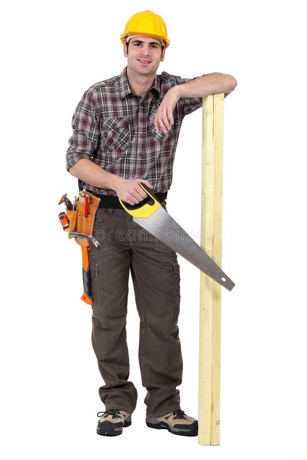 木匠站立与木头 免版税库存图片