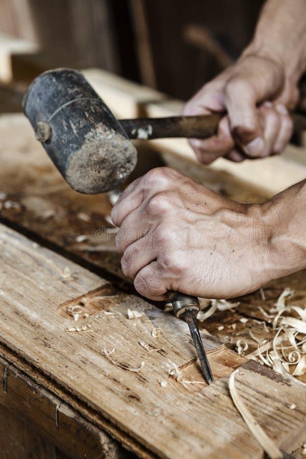 木匠递与凿子和锤子一起使用 库存图片