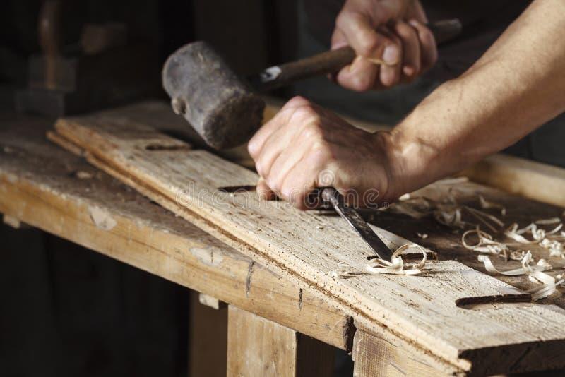 木匠递与凿子和锤子一起使用 免版税库存图片