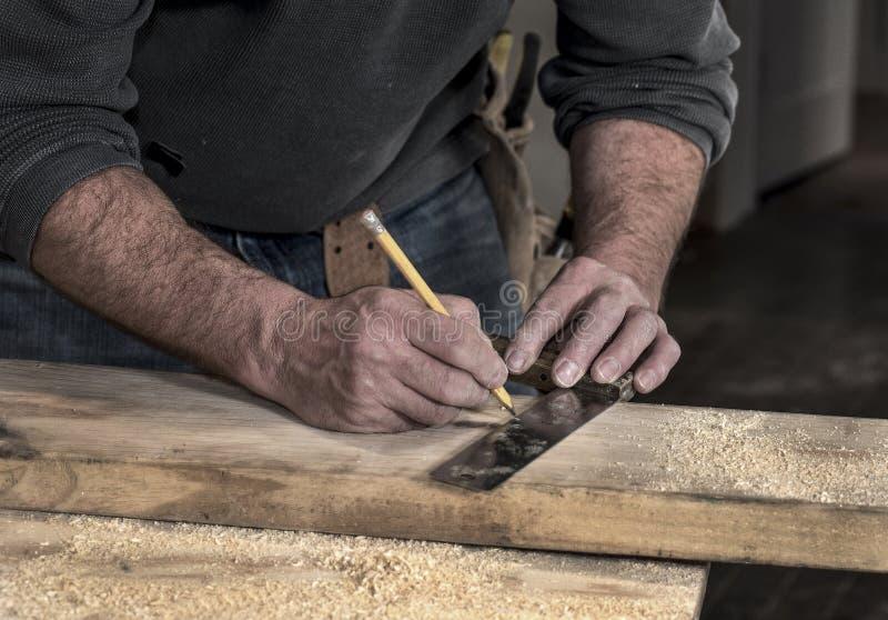 木匠` s概略的坚固性手特写镜头使用标记的铅笔和老的正方形的在木委员会的一条线切开 库存图片