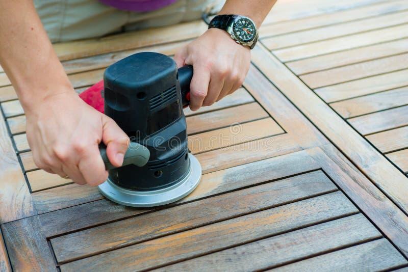 木匠` s特写镜头递与电动砂光机一起使用 图库摄影