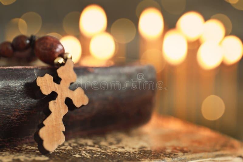木十字架和书反对光 库存照片