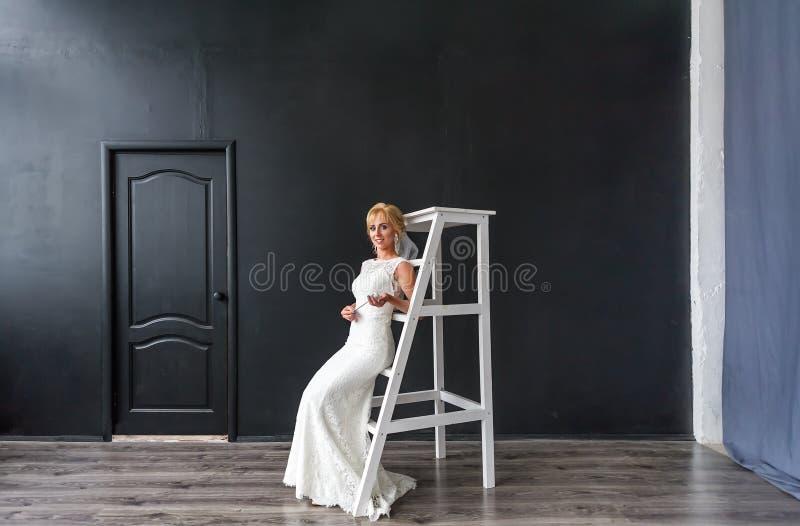 木台阶的美丽的少妇白肤金发的新娘在内部在演播室 库存照片