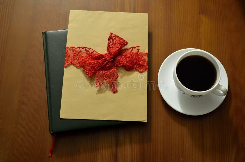 木咖啡杯的表 书和堆信件在背景中 免版税库存照片