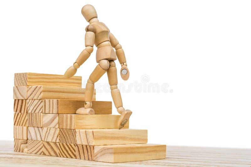 木图攀登一个木楼梯作为事业推进的标志 免版税库存图片