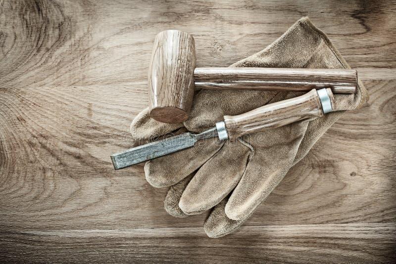 木在木委员会的锤子凿子防护手套 免版税库存照片