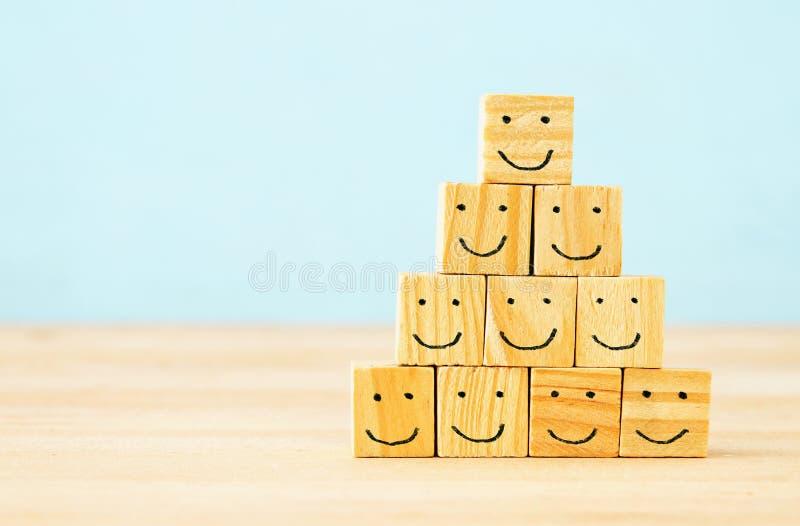 木块的图象与微笑的面对在桌的象,建立一个强的队、人力资源和管理概念 图库摄影