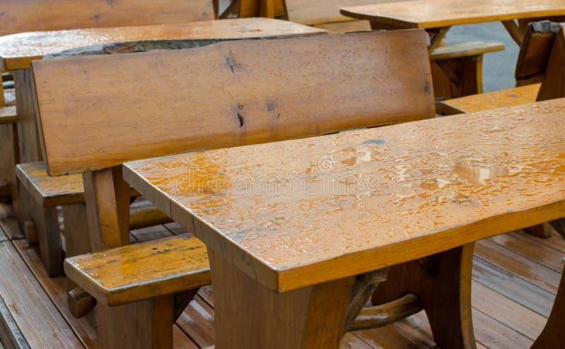木外部用水报道的桌和位子在雨以后 室外咖啡馆长凳和桌在雨以后 免版税库存图片