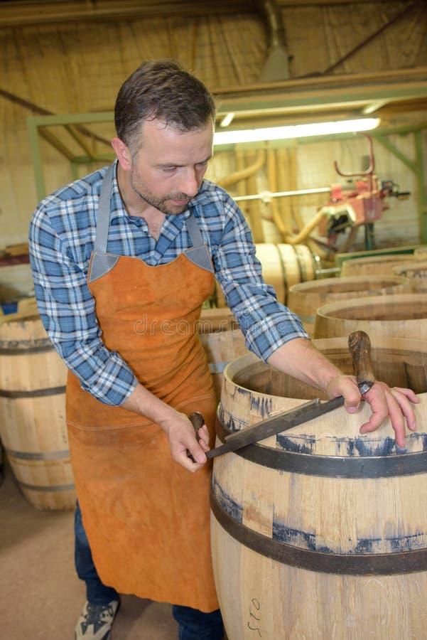 木头滚磨使用锤子和工具的生产木桶匠在车间 库存图片