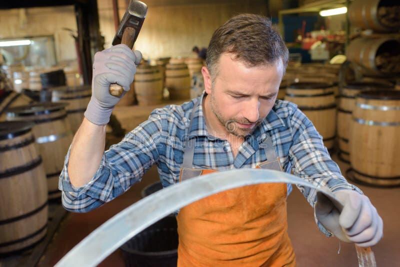 木头滚磨使用锤子和工具的生产木桶匠在车间 免版税库存照片