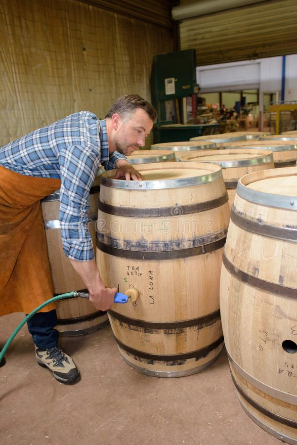 木头滚磨使用锤子和工具的生产木桶匠在车间 免版税图库摄影