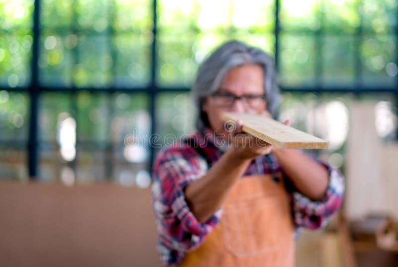 木头老工匠举行splat的模糊的照片并且通过看得检查木头的线性和优良品质 免版税库存图片