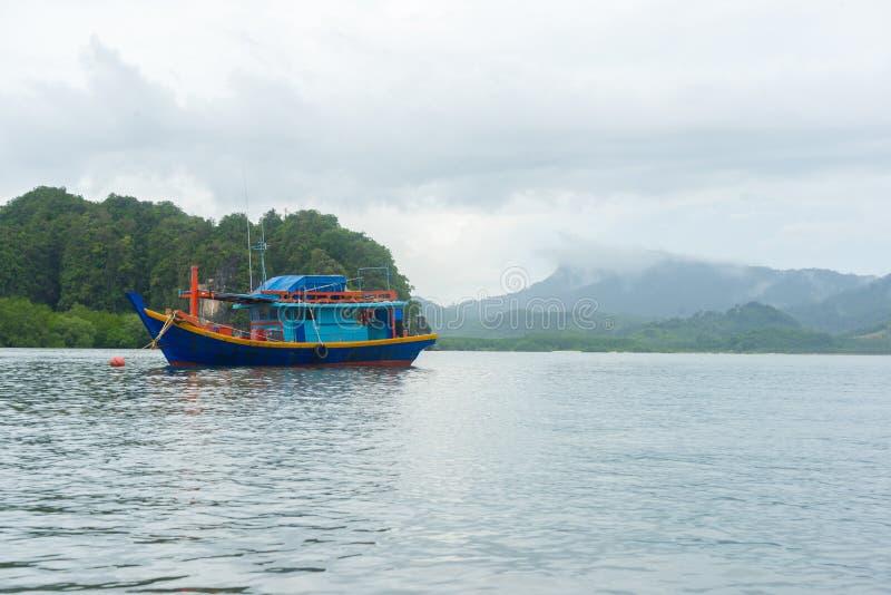 木小船在海有山和云彩背景 库存图片