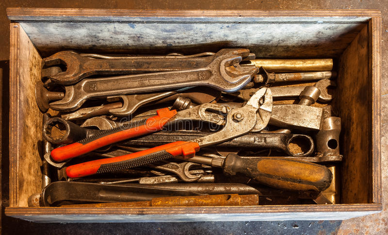 木工具箱有老和肮脏,生锈板钳、圆环扳手、钳子、螺丝刀,凿子和其他的手工具做它 库存照片