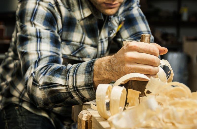 木工飞行的木头在他的车间 免版税库存照片