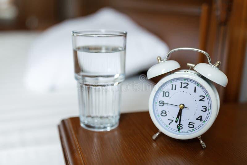 木床头柜上有白色闹钟和一杯水 早 免版税库存照片