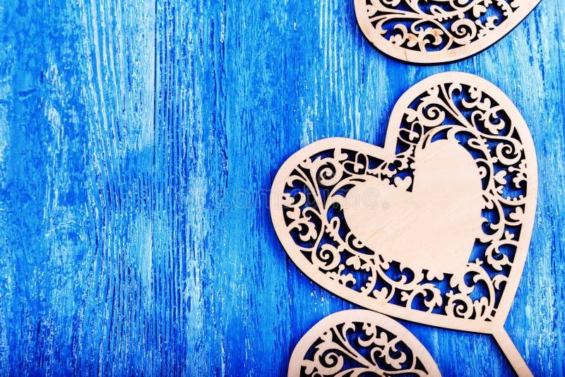 木心脏在蓝色木背景雕刻了 库存照片