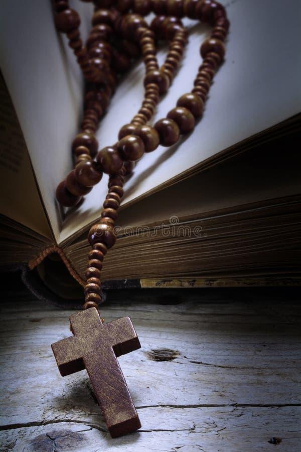 木念珠成串珠状与在一本旧书的十字架在土气木头,关于 免版税库存图片