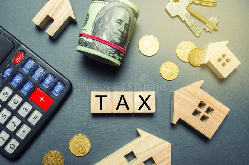 木房子、一个计算器、钥匙、硬币和块与词税 财产税 演算在住宅税的利益 库存照片