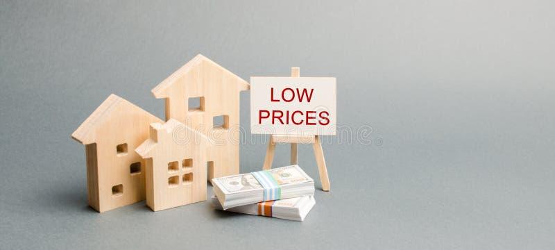 木房子和一张海报与词低价 减少不动产的价值的概念 更低的抵押利息 免版税库存图片