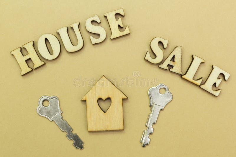 木房子和两把钥匙,题字'销售房子 库存照片