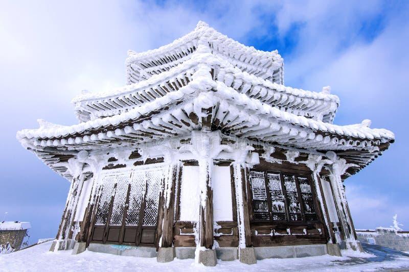 木房子由雪在冬天, Deogyusan山盖 免版税图库摄影