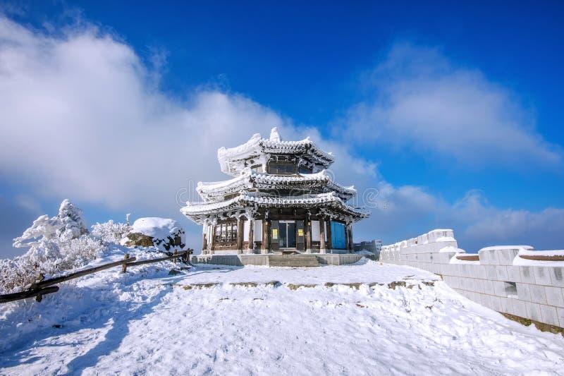 木房子由雪在冬天, Deogyusan山S盖 免版税图库摄影