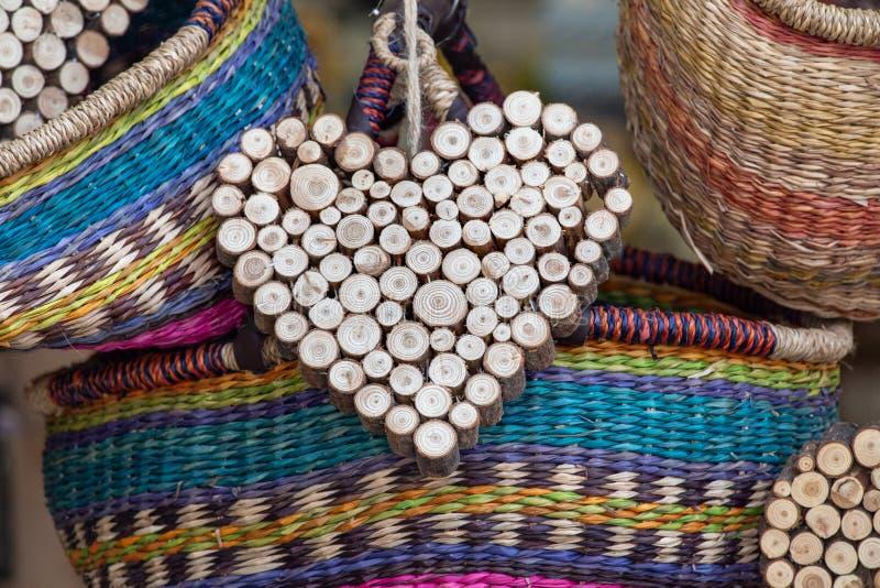 木手工制造心脏装饰品,与五颜六色的柳条筐,在销售中 房子或礼物的装饰 库存照片
