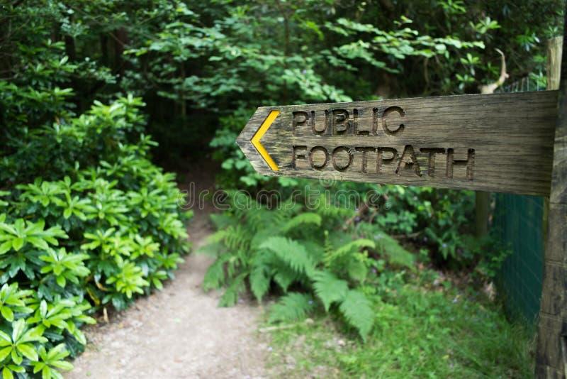 木指向往进入木头的道路的fingerpost公开小径标志 免版税图库摄影