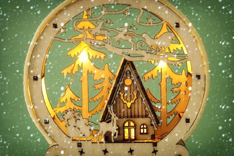 木杉木森林、小屋和圣诞老人不可思议的圣诞节场面的图象在雪橇与鹿 库存照片