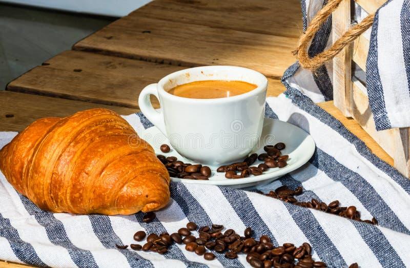 木板箱上的酥皮糕点、咖啡杯和黄油法式羊角面包 食物和早餐概念 咖啡甜点和 免版税图库摄影
