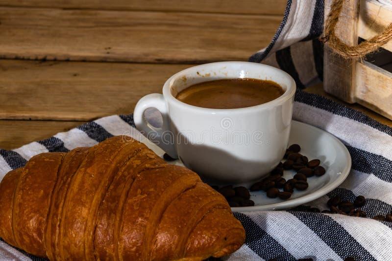 木板箱上的酥皮糕点、咖啡杯和黄油法式羊角面包 食物和早餐概念 咖啡甜点和 免版税库存图片