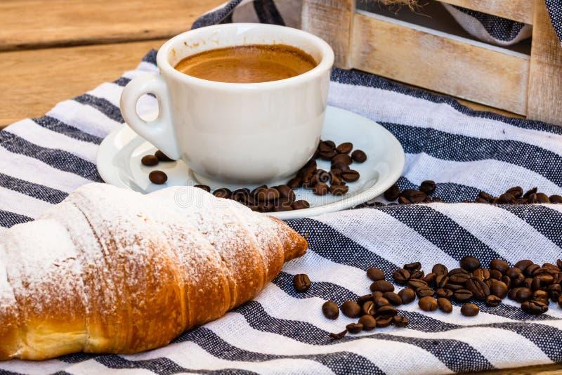 木板箱上的酥皮糕点、咖啡杯和黄油法式羊角面包 食物和早餐概念 咖啡甜点和 库存照片