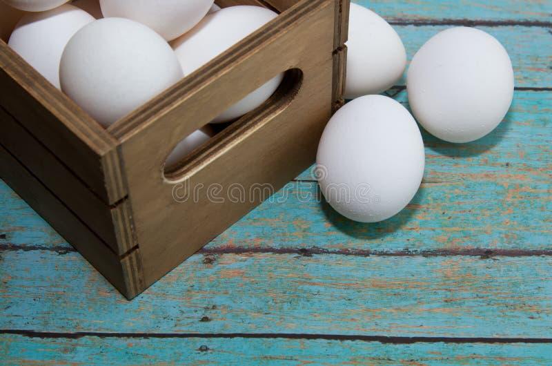 木板箱在木板条背景板的新鲜的鸡蛋 免版税库存图片
