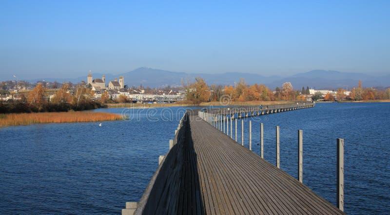 木板走道和拉珀斯维尔遥远的看法,秋天场面 免版税库存图片