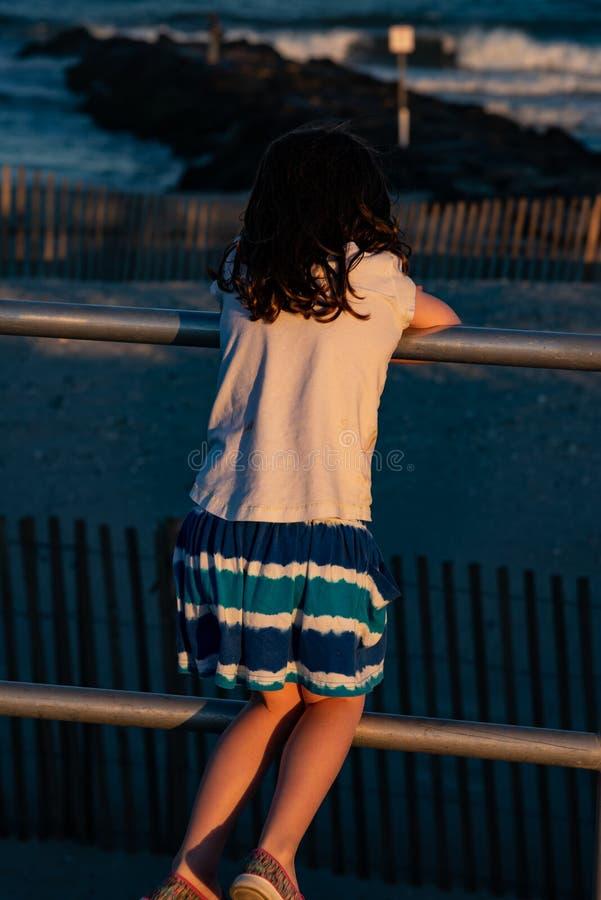 木板走道的年轻逗人喜爱的小女孩有回到看往海洋海浪的照相机的 免版税库存照片
