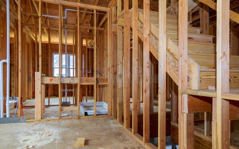 木构架房子,棍子修造了有木捆、岗位和射线框架的家庭建设中新的修造屋顶 库存图片