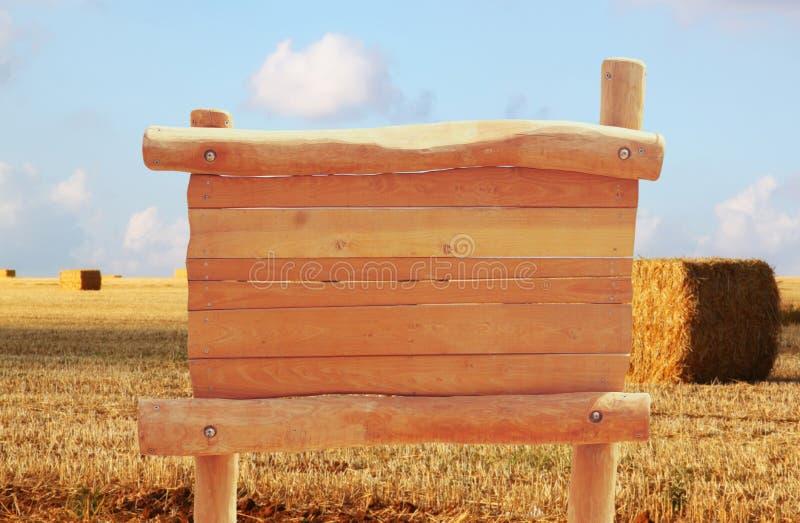 木标志的图象在农村麦田风景前面的 库存图片