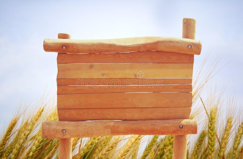 木标志的图象在农村麦田风景前面的 免版税图库摄影