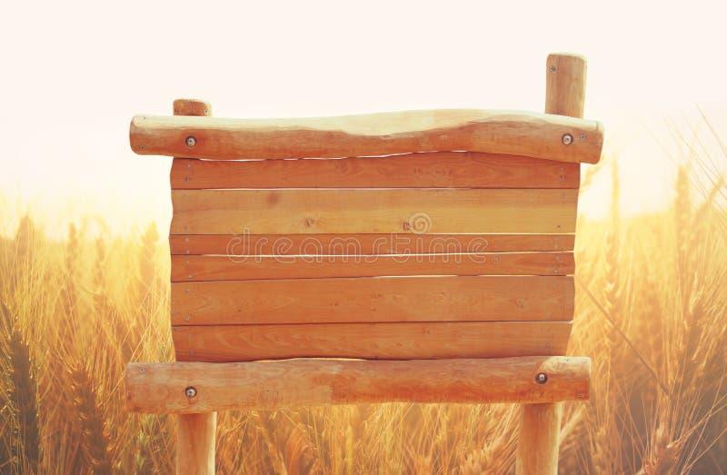 木标志的图象在农村麦田风景前面的 免版税库存照片