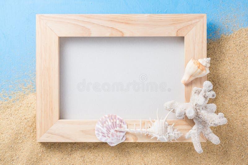 木框架和壳在沙子和蓝色 库存照片