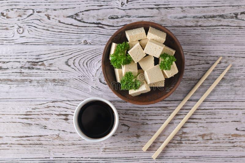 木桌上的陶碗里的筷子和豆腐奶酪 豆奶酪 平躺 图库摄影