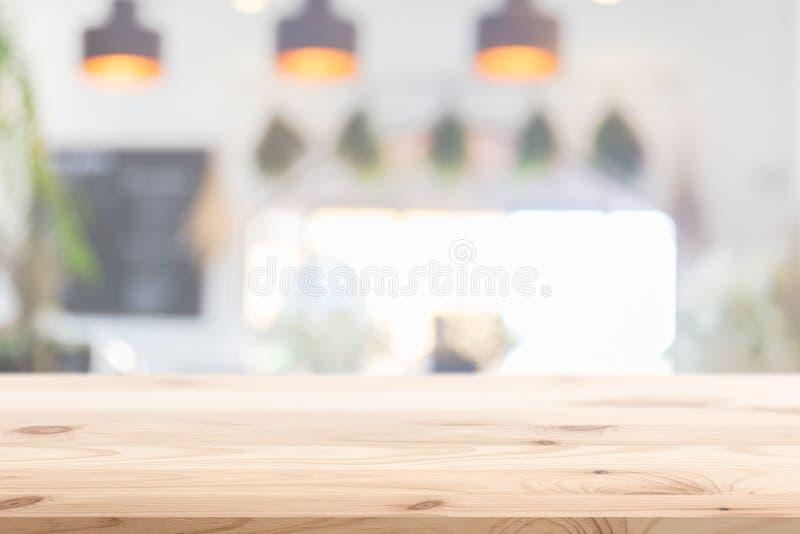 木桌前景有迷离家咖啡馆厨房背景 库存图片
