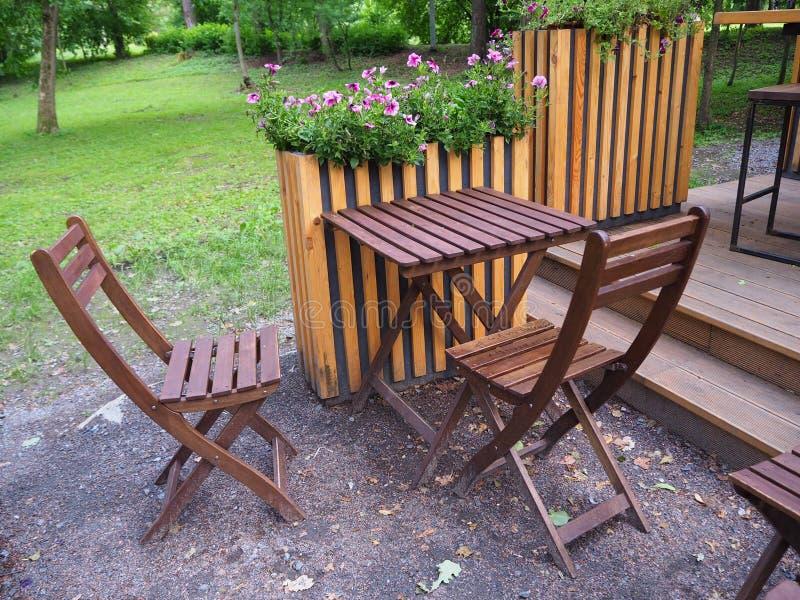 木桌和椅子在街道夏天咖啡馆大阳台在公园 库存图片