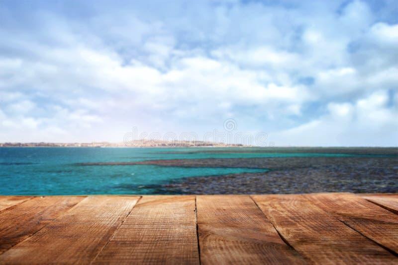 木桌在海洋和天空的背景中 免版税库存照片
