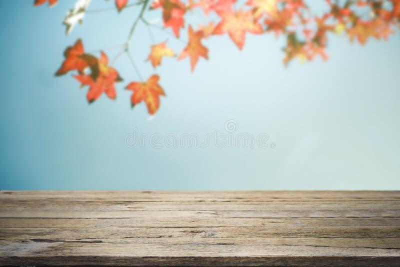 木桌或大阳台和红色叶子在蓝天背景 免版税库存图片